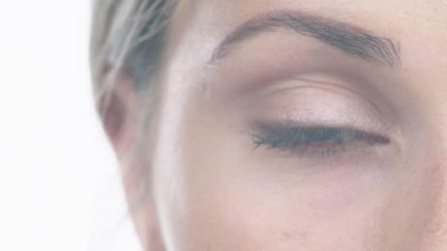 vídeos de stock, filmes e b-roll de vídeo 4k de olhos de uma jovem atraente contra um fundo de estúdio branco - olhos verdes