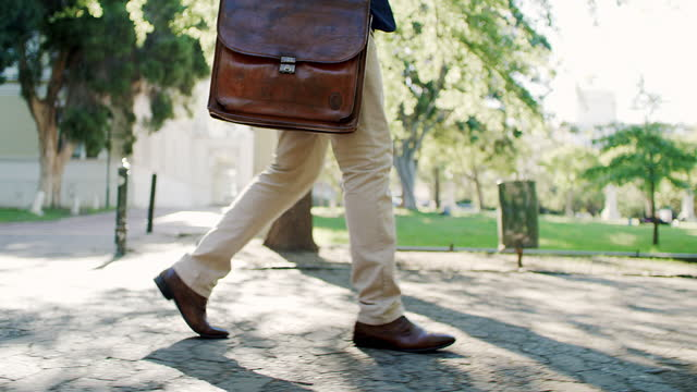 4k video footage of an unrecognisable businessman walking outdoors - side view stock videos & royalty-free footage