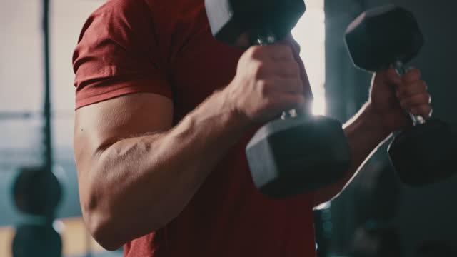 ジムでダンベルで二頭筋カールエクササイズをしている認識できない男の4kビデオ映像 - 丸くなる点の映像素材/bロール