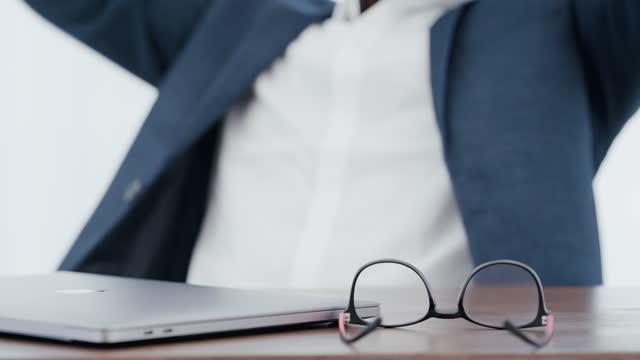 vídeos y material grabado en eventos de stock de imágenes de video de 4k de un joven empresario irreconocible poniendo sus manos detrás de su cabeza después de un buen día de trabajo en la oficina - lente