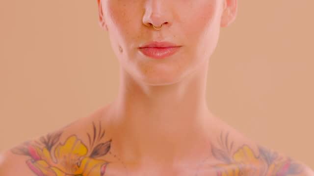 vidéos et rushes de vidéo 4k d'une jeune femme méconnaissable posant avec son doigt sur ses lèvres en studio sur un fond de couleur crème - vidéo portrait