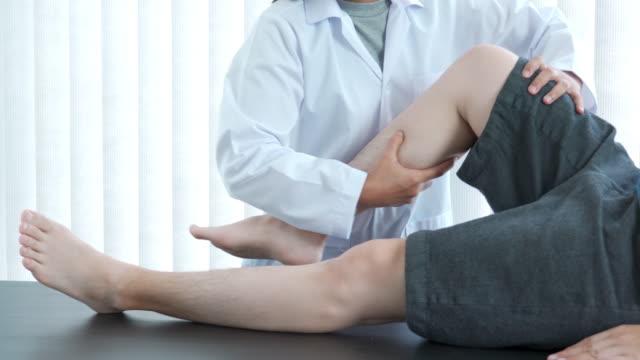 vídeos de stock, filmes e b-roll de 4k vídeo de vídeo de médico fisioterapeuta dando tratamento ao paciente da perna e dando joelho exercitando-se no hospital - physical injury