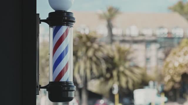 4k videoaufnahmen von rotierenden, gestreiften friseurstangen vor einem friseurladen während des tages - pfosten stock-videos und b-roll-filmmaterial