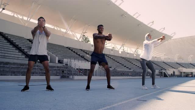vídeos y material grabado en eventos de stock de imágenes de video 4k de tres atletas haciendo sentadillas juntos mientras estaban en el estadio - three people