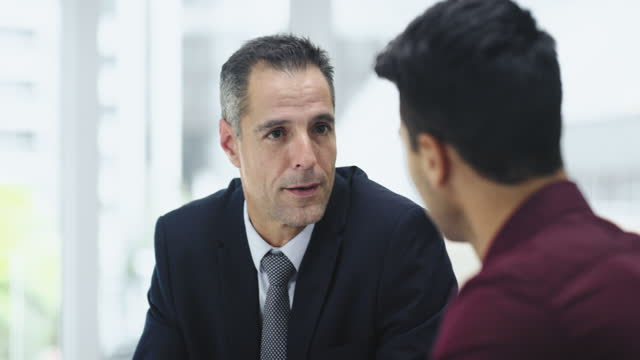 4k video footage of two businessmen having a meeting in a modern office - financial advisor stock videos & royalty-free footage