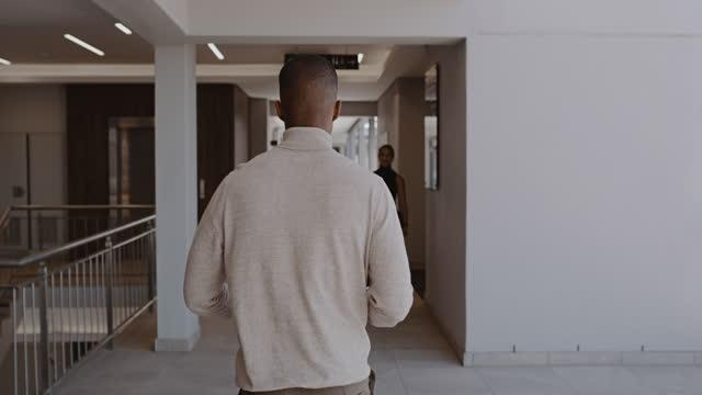 vídeos de stock e filmes b-roll de 4k video footage of two coworkers walking by each other at work - atrás