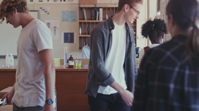 4k videofilmer av två tonårsflickor som chattar medan de går in i ett klassrum med sina kamrater - gå in bildbanksvideor och videomaterial från bakom kulisserna