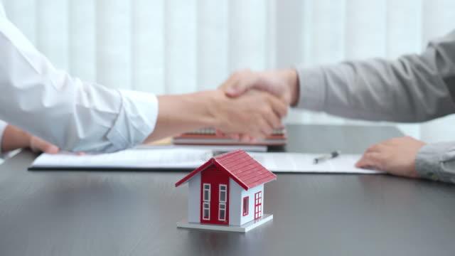 4k videofilmer av unga asiatiska affärsman mäklare agent erbjuda hus köpekontrakt för att köpa ett nytt hem för att diskutera med klient undertecknande kontrakt dokument och skaka hand på kontoret - sälja bildbanksvideor och videomaterial från bakom kulisserna