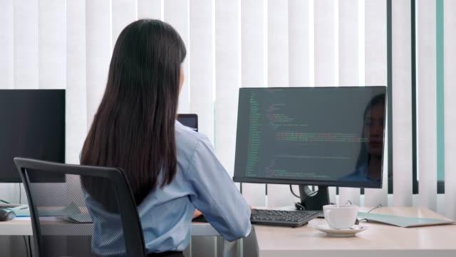 4k videofilmer av unga asiatiska kvinna programmerare läsa och arbeta på dator med kodning utveckling webbdesign och utveckla teknik - binär kod bildbanksvideor och videomaterial från bakom kulisserna