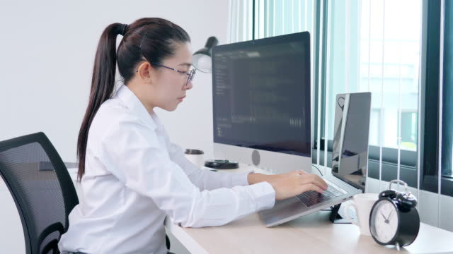 4k video footage of young asian woman programmer reading and working on computer with coding development website design and developing technology - computer language stock videos & royalty-free footage