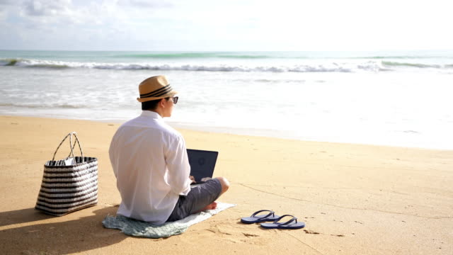 4k video footage of young man using laptop working near waterfront and looking sea view while relaxing on the beach - summer stock videos & royalty-free footage