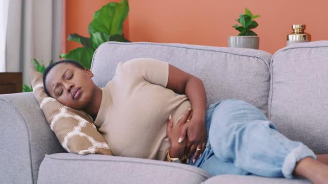 自宅のソファに横たわっている間に胃の痛みを経験している若い女性の4kビデオ - 人の腸点の映像素材/bロール