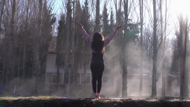 4k video of adult woman doing yoga exercises in foggy outdoor - sun salutation stock videos & royalty-free footage