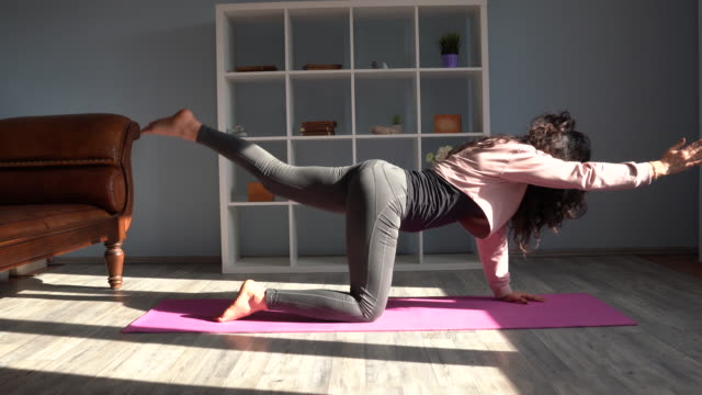 4k video of adult woman doing yoga exercises in living room - middle east stock videos & royalty-free footage