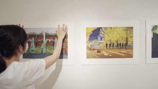 vídeos y material grabado en eventos de stock de vídeo 4k de una mujer asiática preparándose para la exposición de pintura - cámara en mano