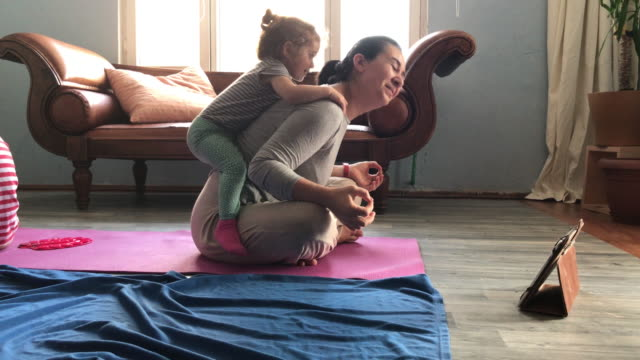 4k video of mother meditating while her son and baby daughter are playing around - 6 7 years stock videos & royalty-free footage