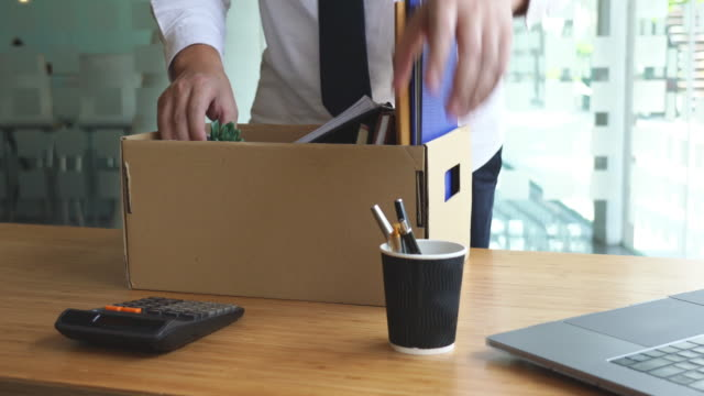 4k video of unhappy employee packing his belongings into cardboard box and leaves office - demobilisation stock videos & royalty-free footage