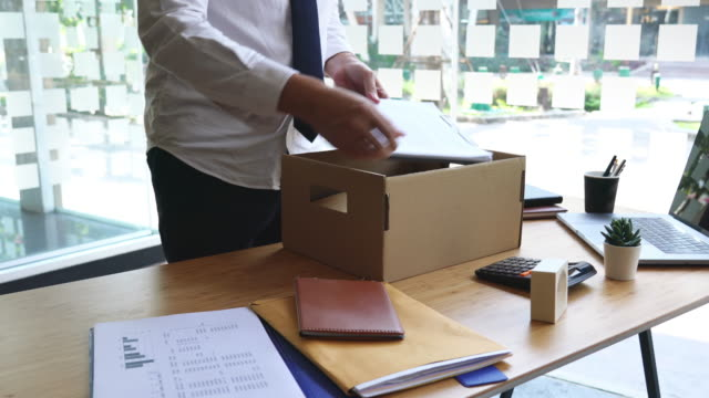 4k video of unhappy employee packing his belongings into cardboard box and leaves office - unemployment stock videos & royalty-free footage