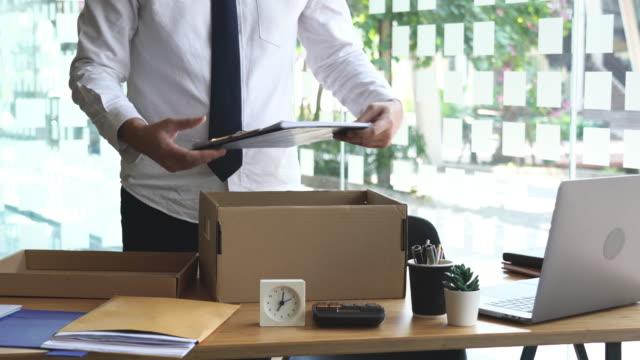stockvideo's en b-roll-footage met 4k video van ongelukkige werknemer die zijn bezittingen in kartondoos verpakt en bureau verlaat - karton