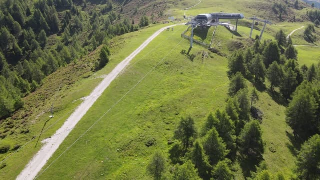 4k video shooting with drone of mountain panoramas, on the italian dolomites alps. snow-capped peaks, green meadows and ski slopes, mountain trails with small wooden houses. blue skies with clouds. - video stock videos & royalty-free footage
