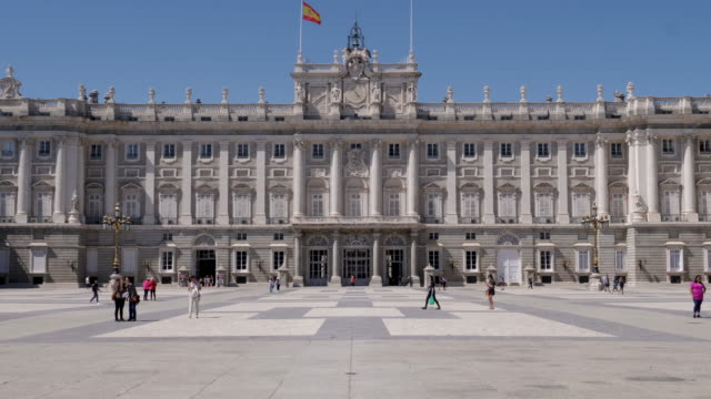 4k view of royal palace of madrid front entrance and facade. tourists taking photos and selfies in the plaza outside. - palace stock videos & royalty-free footage