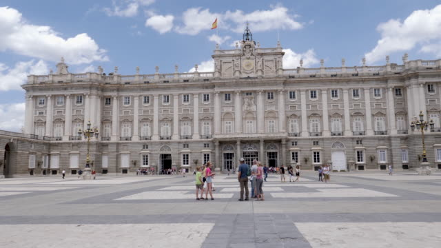 vídeos de stock e filmes b-roll de 4k view of royal palace of madrid front entrance and facade. tourists taking photos and selfies in the plaza outside. - palace