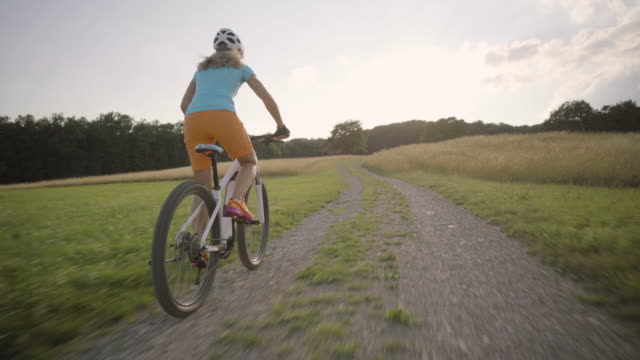 4k woman cycling on electric mountain bike summer sunset rural landscape