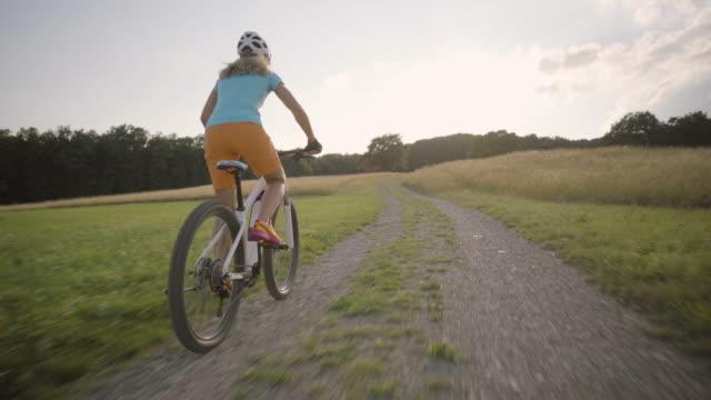 vidéos et rushes de 4k woman cycling on electric mountain bike summer sunset rural landscape - quadragénaire