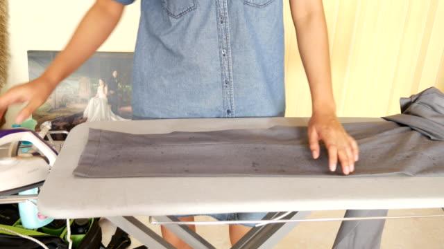 vídeos y material grabado en eventos de stock de 4 k : mujer planchado de ropa - plancha