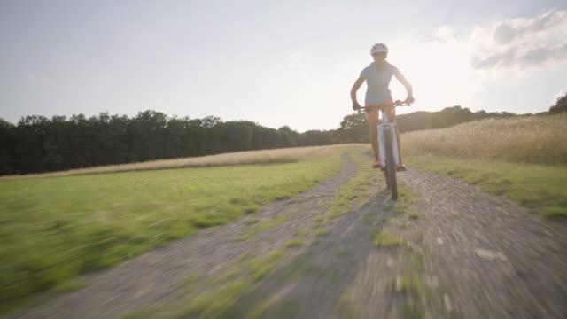 4k woman on  mountain bike following camera in rural landscape in summer