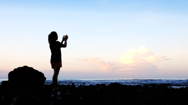 vídeos y material grabado en eventos de stock de 4k: mujer relaja con smartphone tomar fotos en la playa - espalda partes del cuerpo