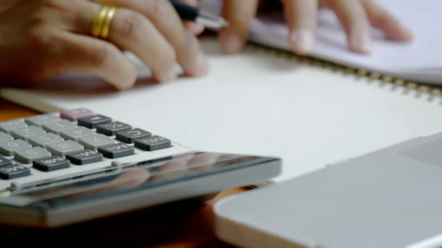 4k Woman using calculatior of financial data analyzing. Hand with pen on calculator.