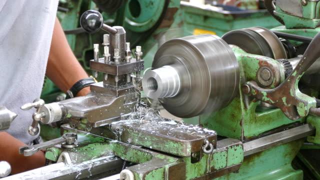 stockvideo's en b-roll-footage met 4k: werknemer draaien deel door handmatige draaibank machine. - productielijn werker