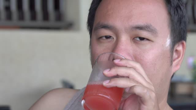4k: junger asiatischer Mann Saft zu trinken