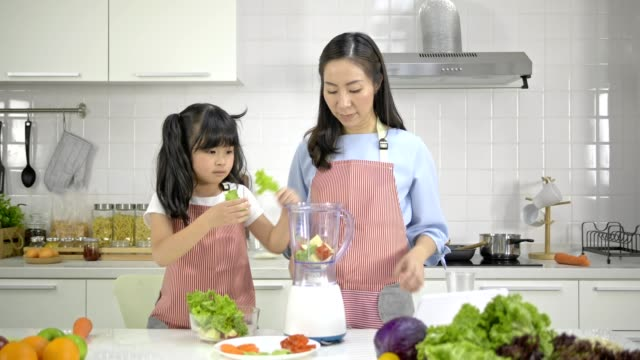 vídeos de stock e filmes b-roll de 4k ,young asian mother and daughter happy and fun preparing vegetable and fruits salad in a modern white kitchen.cheerful daughter when cooking. - pratos vegetarianos