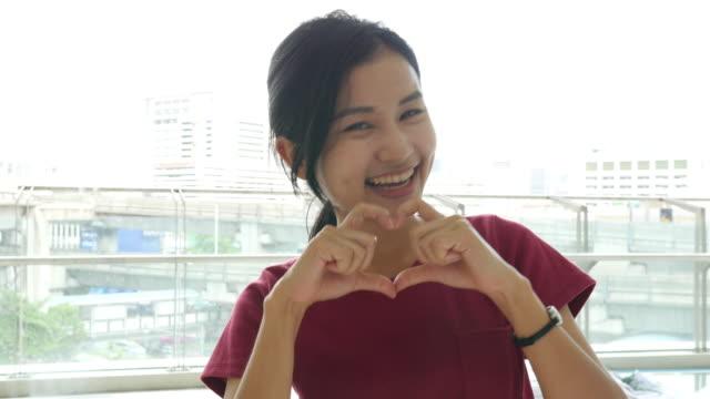 4k: young woman making heart shape