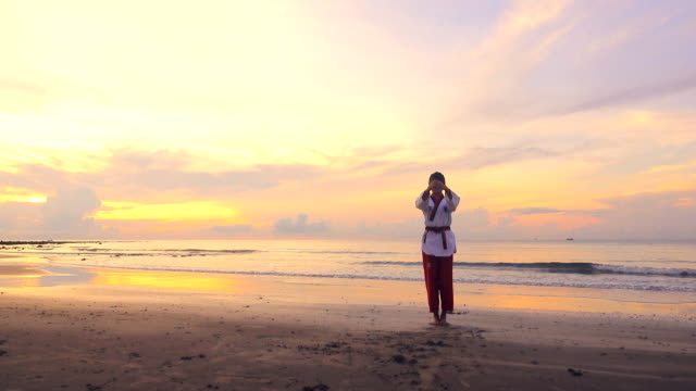4k: young women practising martial arts outdoors on the beach at sunset - martial arts stock videos & royalty-free footage