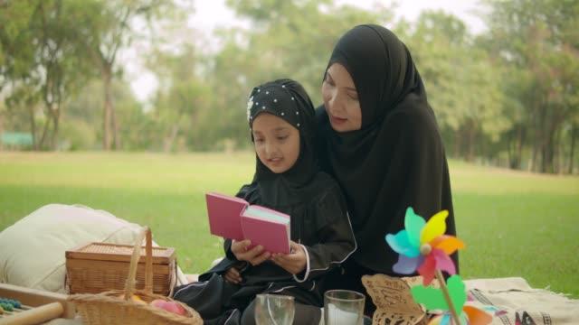 vidéos et rushes de 4k/60fps , heureux asiatique mère musulmane et fille de lecture et d'écriture au parc public le week-end holiday.wear hijab. - vêtement religieux