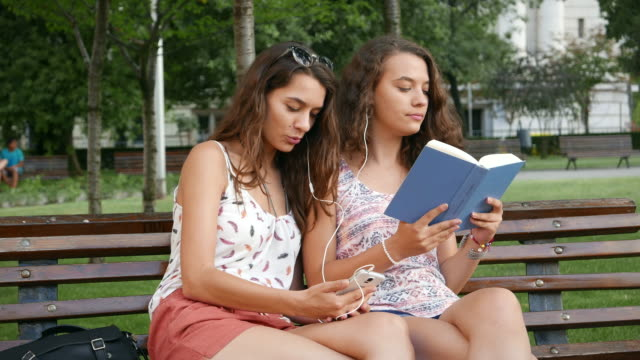 音楽を聴く、読書公園でリラックス 4k_sisters - ため息点の映像素材/bロール