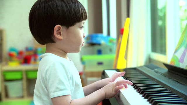 4K:Asian little boy playing practicing the piano in his home.