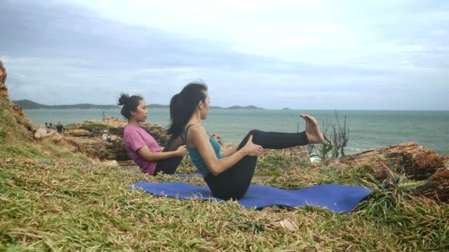 4k, insegnante di yoga asiatico aiuta la giovane donna a praticare yoga sulla collina vicino alla spiaggia tropicale. - dorso umano video stock e b–roll