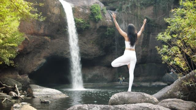 vidéos et rushes de 4k, professeur asiatique de femme de yoga aide la jeune femme à pratiquer le yoga sur la colline près de la plage tropicale. - s'étirer