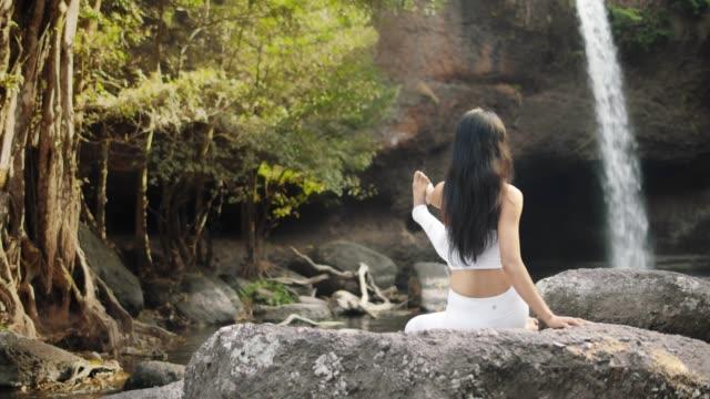 4k, insegnante di yoga asiatico aiuta la giovane donna a praticare yoga sulla collina vicino alla spiaggia tropicale. - praticare video stock e b–roll