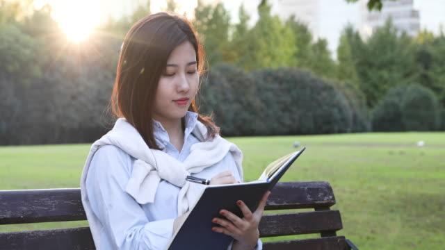 stockvideo's en b-roll-footage met 4k: mooi aziatisch meisje leesboek op park, shanghai, kin - 20 24 years