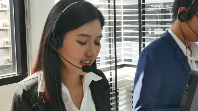 4 k: 美しいアジアの女性オペレーターの笑顔 - 受付係点の映像素材/bロール
