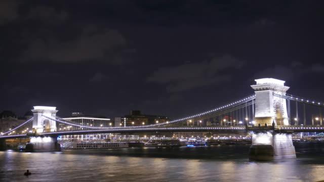 vídeos de stock e filmes b-roll de 4 k: budapest hungria cadeia ponte na noite, time-lapse de movimento - ponte széchenyi lánchíd