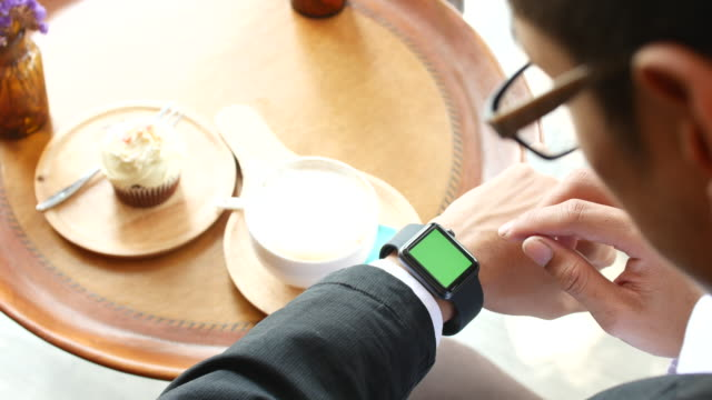 4K:Business man using smart watch in coffee shop,Green screen