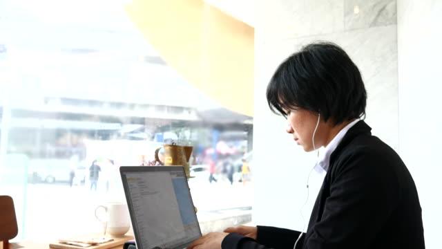 4 K :  Geschäft Frau Tippen Sie Ihr Laptop und Musik hören