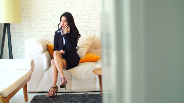 4K:Businesswoman on cellphone sitting in her room.