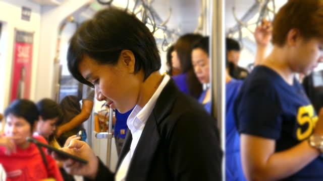 4K:Businesswoman using smartphone on train